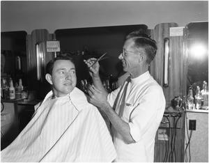 Primary view of object titled 'S.J. Middleton receiving a haircut'.