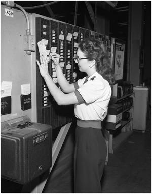 Primary view of object titled 'Nell Polson checking the time cards'.