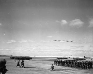 Primary view of object titled 'Eighth Air Force Airmen marching in reviw of ramp with 11 B-36's overhead'.