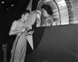 Primary view of object titled '[Two Women Performing Mechanical Work on an Aircraft]'.