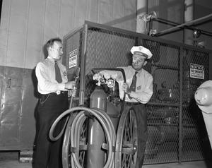 Primary view of object titled '[Two Men Inspecting a Dugas Fire Extinguisher]'.