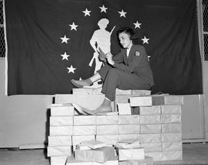 Primary view of object titled '[Iva McMurray Sitting on a Stack of Paper Bonds]'.