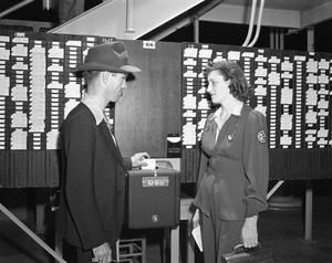Primary view of object titled '[Two People Standing by a Time Clock]'.