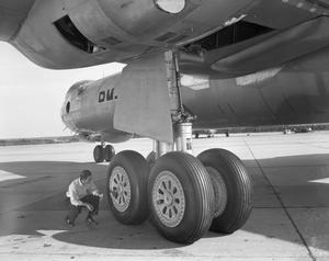 Primary view of object titled '[J.E. Massey Inspects Landing Gear]'.