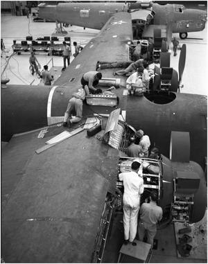 Primary view of object titled '[Men Working on an Airplane Wing]'.