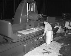 Primary view of object titled '[Man running the grinding machine]'.