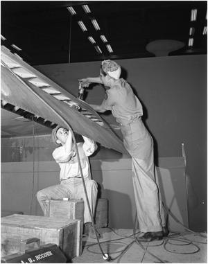 Primary view of object titled 'Man and Woman Riveting on Airplane Wing'.