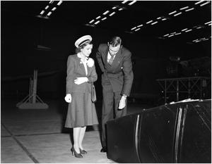 Primary view of object titled '[George Newman and Helen Hayes inspecting a gas tank]'.