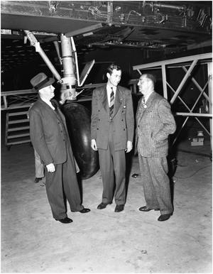 Primary view of object titled '[Mr. Newman and Mr. Fleet in front of B-24 wheel]'.