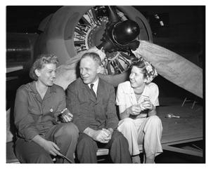 Primary view of object titled '[Two Women and a Man Sitting Next to an Aircraft Propeller]'.
