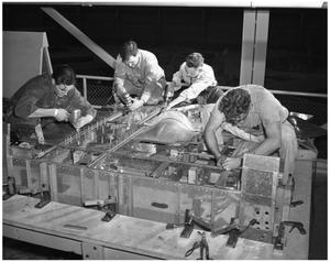Primary view of object titled '[Four Men Working on the Nose of a Fuselage]'.
