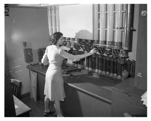 Primary view of object titled '[Dorothy Keys Operating Tube Station in the Mail Room]'.