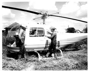Primary view of object titled 'Cowboys Looking at a Bell Helicopter on the SMS Ranch'.