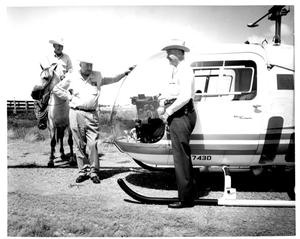 Primary view of object titled 'W.G. Swenson and Two Cowboys Admiring a Helicopter'.