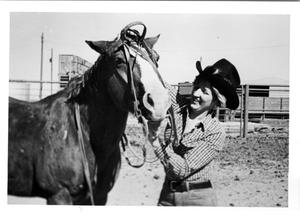 Primary view of object titled 'Cowgirl Putting a Bridle on a Horse'.