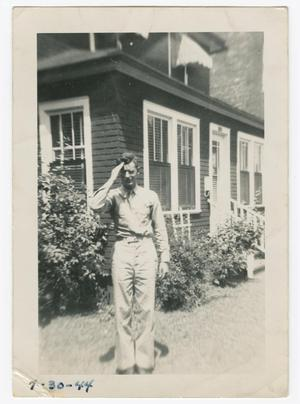 Primary view of object titled '[William Giannopoulos Saluting in Front of a House]'.