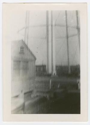 Primary view of object titled '[Wooden Building at the Base of a Water Tower]'.