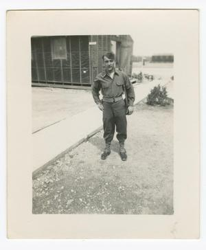 Primary view of object titled '[Soldier Standing by a Building and Sidewalk]'.