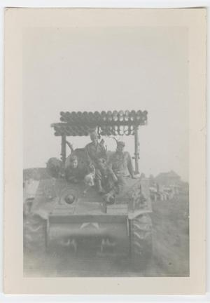 Primary view of object titled '[Three Soldiers Sitting Under a T-34 Calliope Rocket Launcher]'.
