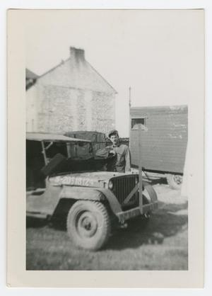 Primary view of object titled '[William Giannopoulos Holding a Jeep's Armor Plate]'.