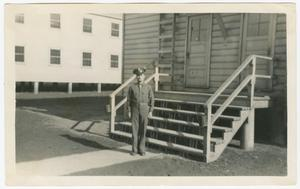 Primary view of object titled '[Ed Scott Standing by Barracks]'.