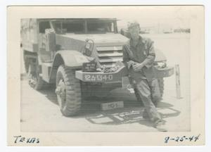Primary view of object titled '[William Giannopoulos Leaning on a Half-Track]'.