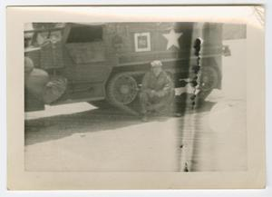 Primary view of object titled '[William Giannopoulos Sitting on a Half-Track's Track]'.