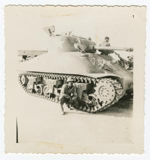 Primary view of object titled '[William Giannopoulos Crouching Beside a Tank]'.
