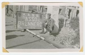 Primary view of object titled '[Soldier Beside a Sign for the Brenner Pass]'.