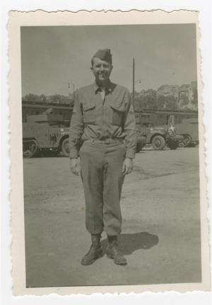 Primary view of object titled '[Lee Kropff Standing by Half-Tracks]'.