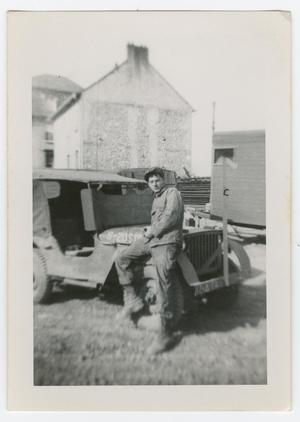 Primary view of object titled '[William Giannopoulos Sitting on a Jeep]'.