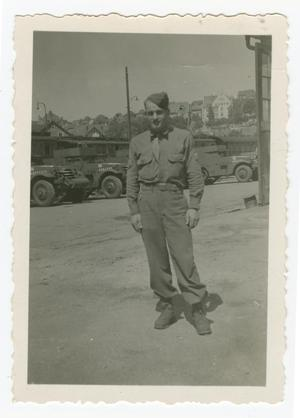 Primary view of object titled '[Ovie Sanders Standing in Front of Jeeps]'.