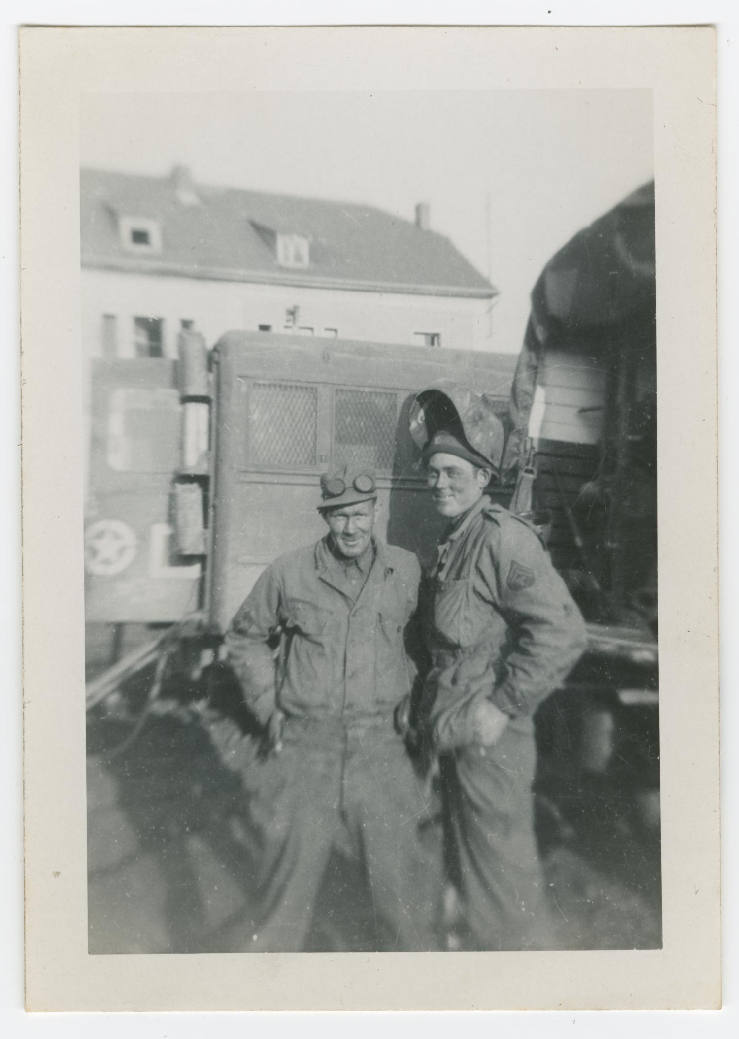 [Two Soldiers Standing Between Trucks]                                                                                                      [Sequence #]: 1 of 2