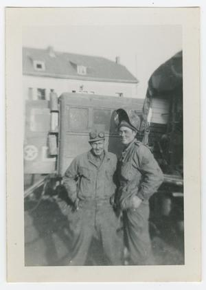 Primary view of object titled '[Two Soldiers Standing Between Trucks]'.