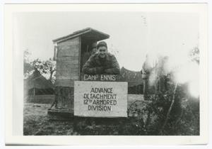 Primary view of object titled '[Sergeant John Pilarski Leaning on a Camp Ennis Sign]'.