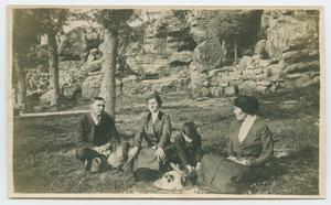 [Photograph of People Sitting by a Rock Slope]