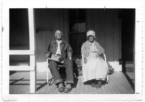 Mr. and Mrs. Henry Wolf sitting on their Porch