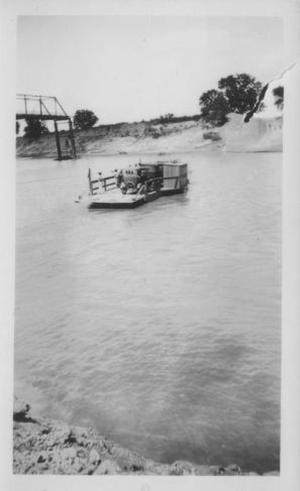 Primary view of object titled '[The ferry (with two automobiles on it) crossing the Brazos River.]'.