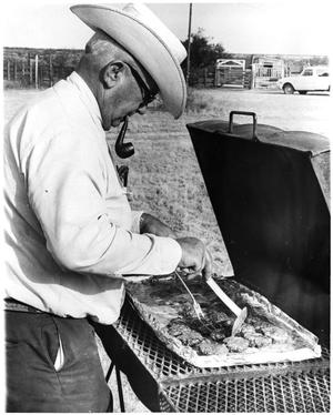 Primary view of object titled 'Man Cooking Meat on a Grill'.