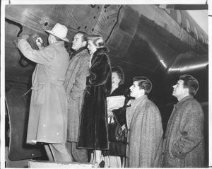 Primary view of object titled '[Bob Hope and other performers writing their autographs on an airplane]'.