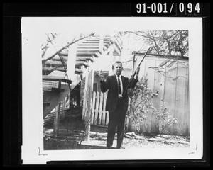 Primary view of object titled 'Detective Brown with Rifle in Backyard at 214 Neeley Street #1'.