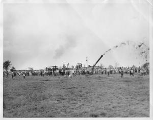 Primary view of object titled '[A rice threshing scene. Large groups of people are standing nearby.]'.