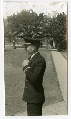 Primary view of object titled 'Side Profile of a Man in Uniform Standing on a Siadewalk'.