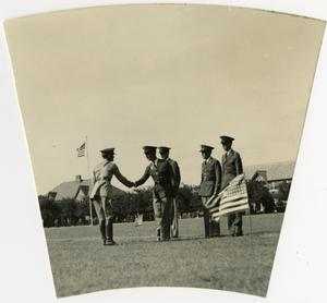 Primary view of object titled 'Two Men in Uniform Shaking Hands in a Field with Three Others Asside'.