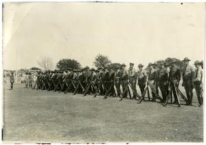 Primary view of object titled 'Miltary Line-Up with Guns Propped Up on the Ground'.