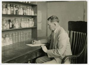 Primary view of object titled 'A Man Writing at a Medicine Desk'.