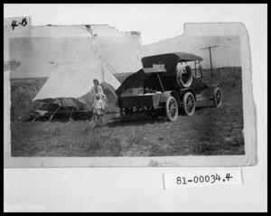 Primary view of object titled 'Woman and Children by Truck with Trailer and Tent'.