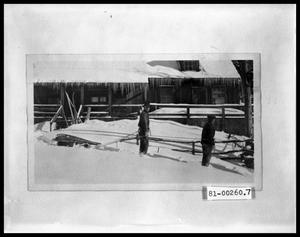 Primary view of object titled 'Two Men Pulling Sled in Front of Cabin'.