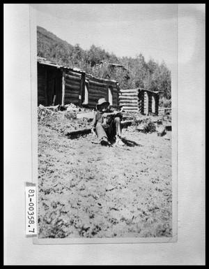 Primary view of object titled 'Old Man Outside Dilapidated Cabin'.