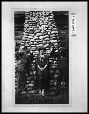 Primary view of object titled 'Two Men with Woman in Front of Stone Chimney on Cabin'.